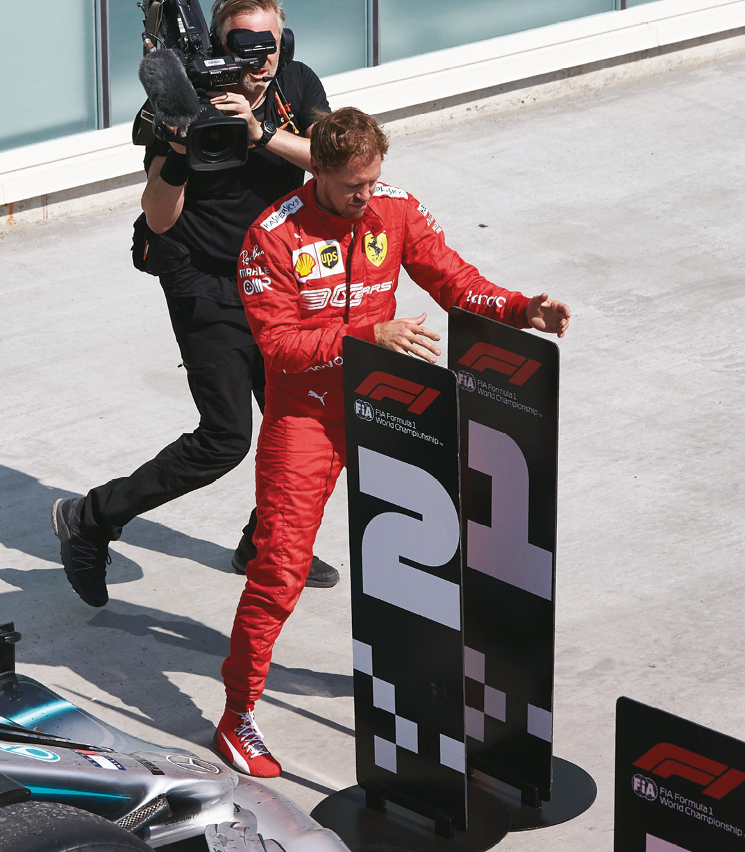 An irate Vettel plays to the crowd by swapping the number boards under the podium in Canada