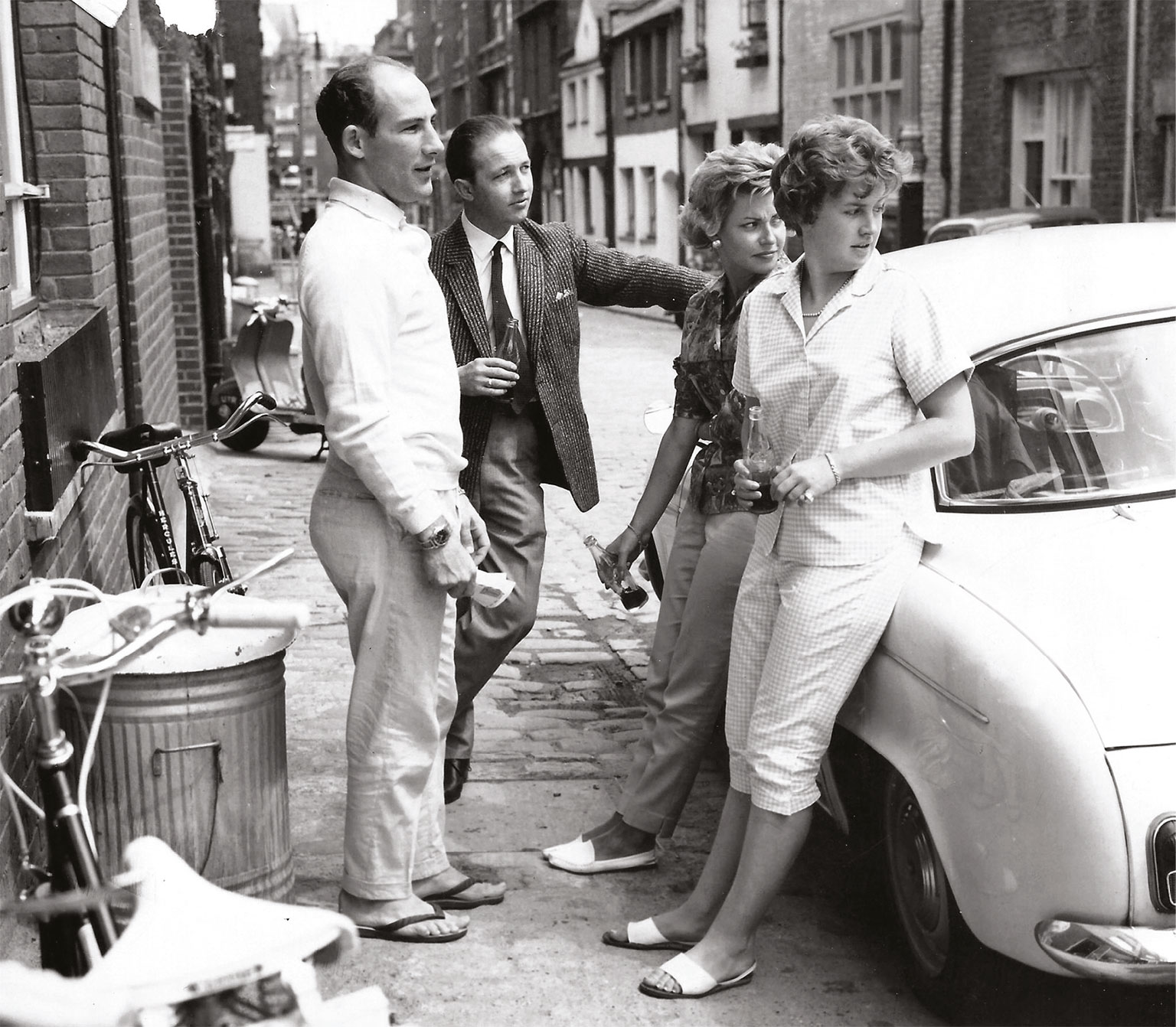 Stirling and Val (in the foreground) about to visit their Belgravia local. The bikes are to exercise Moss's legs after his 1960 Spa accident