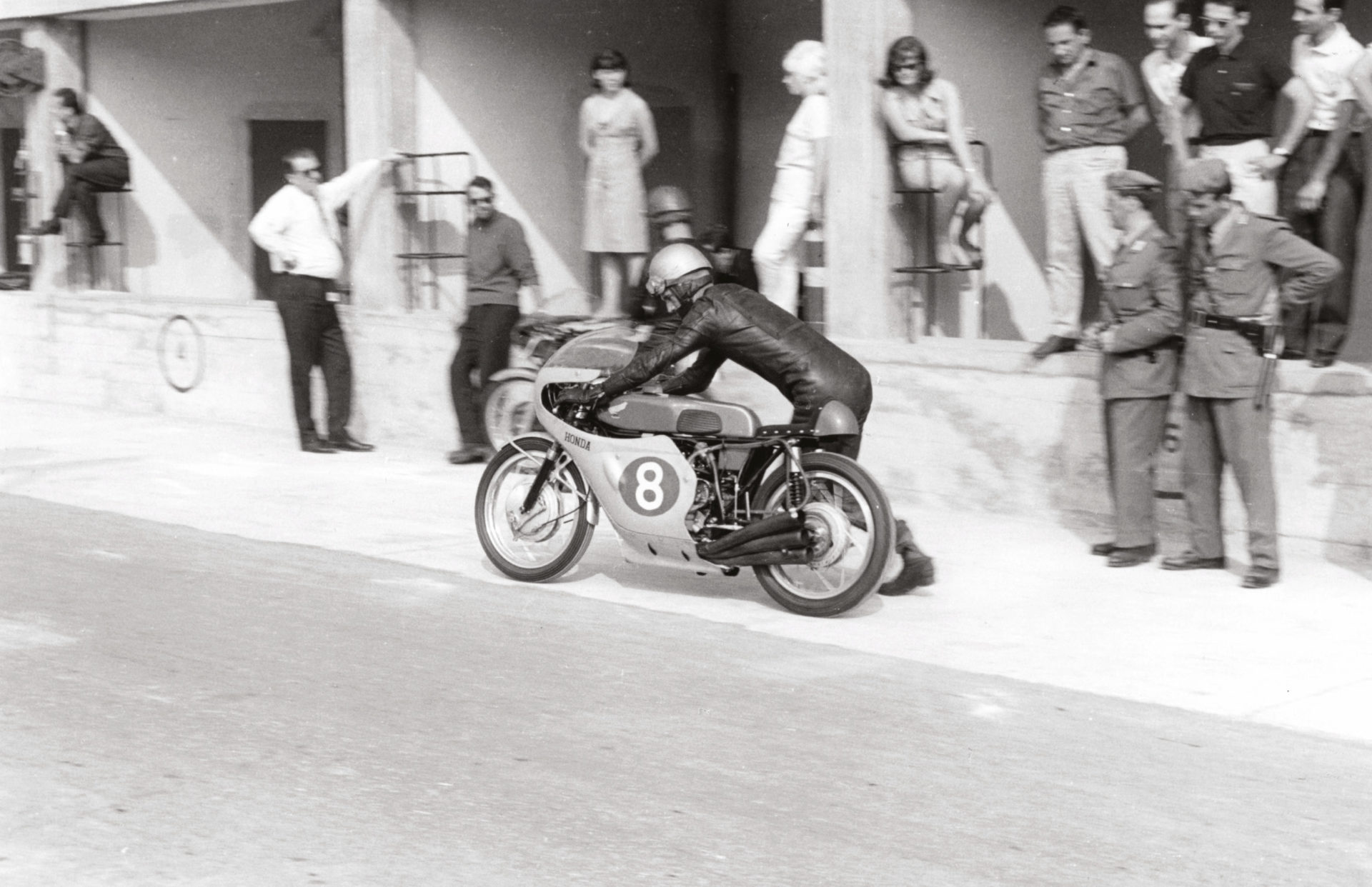"Jim Redman bumps Honda's brand-new 250 six into life at Monza, September 1964. The bike ""sounded like the end of the world"" – it was so loud that Dunlop technicians refused to check its rear tyre when the engine was running"