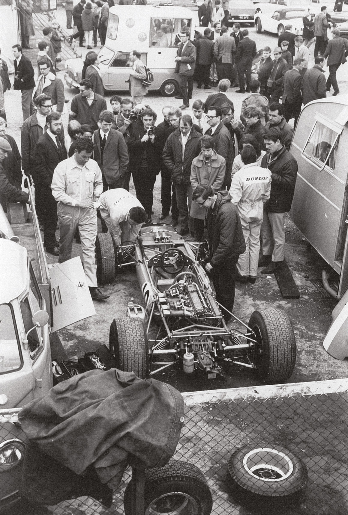 Privateer Bob Anderson's crew tweak his Brabham BT11 beside the VW flat-bed he used as his transporter.