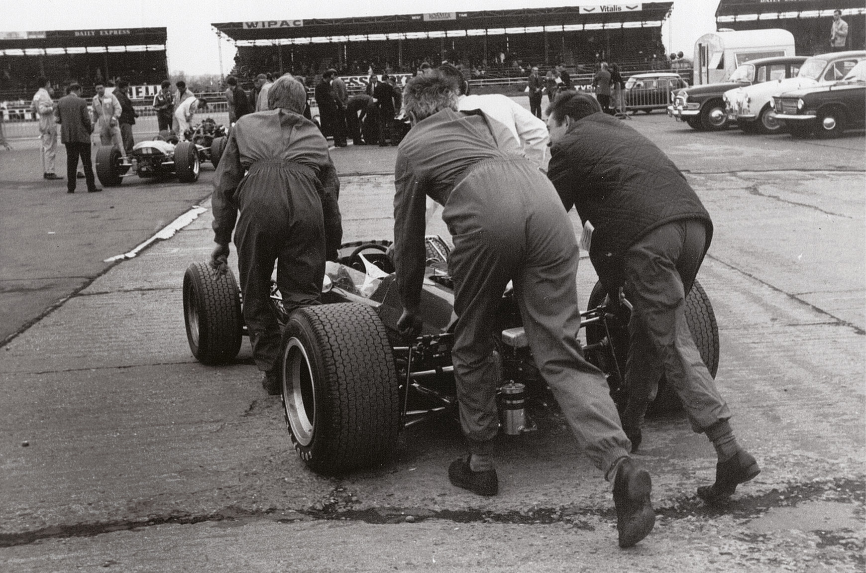 The Bruce McLaren Motor Racing team heads to the collecting area, with Bruce giving a push