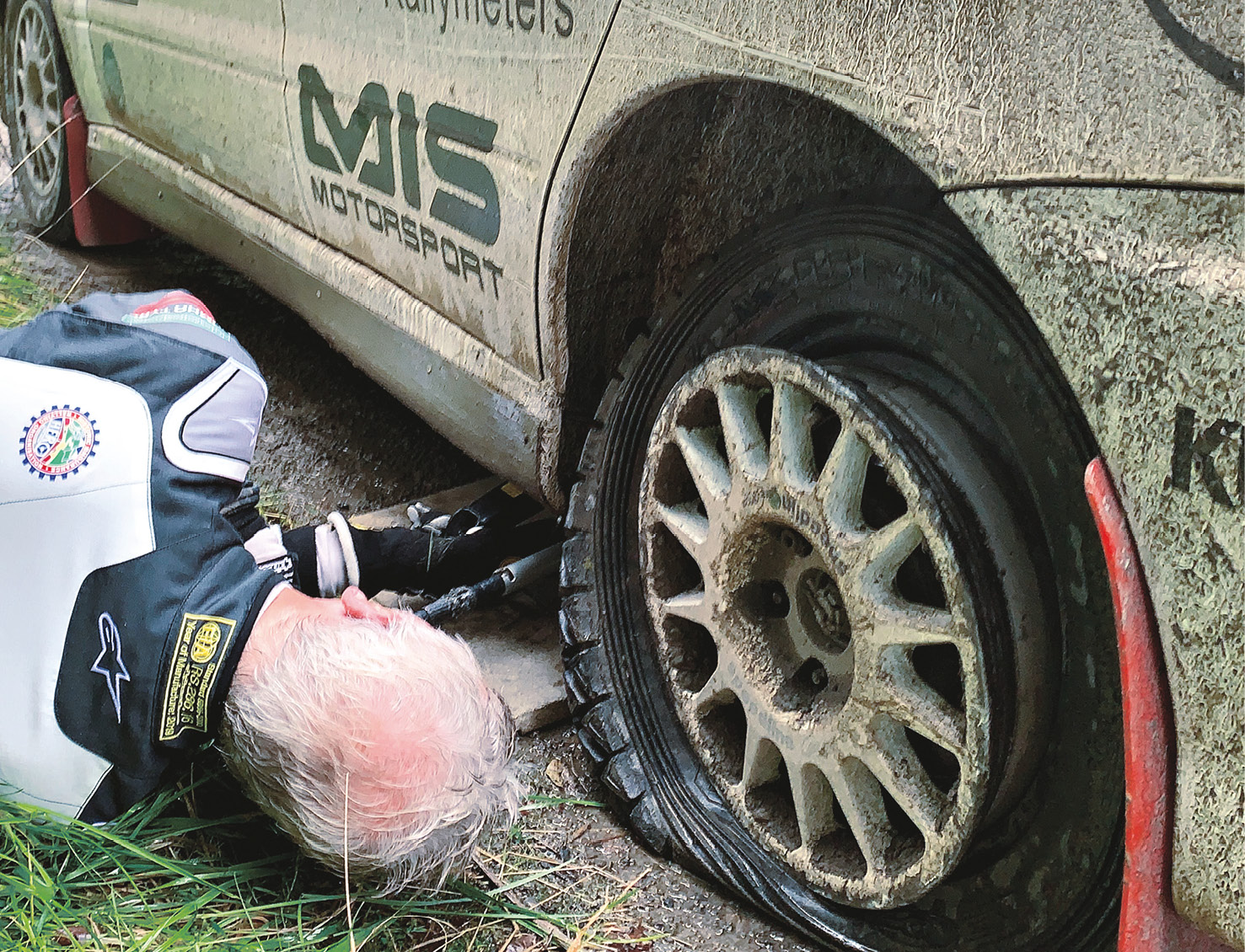 The moment you realise that white overalls weren't a good idea. Jardine gets down to the dirty work to jack up the Evo and replace a rear puncture that cost time