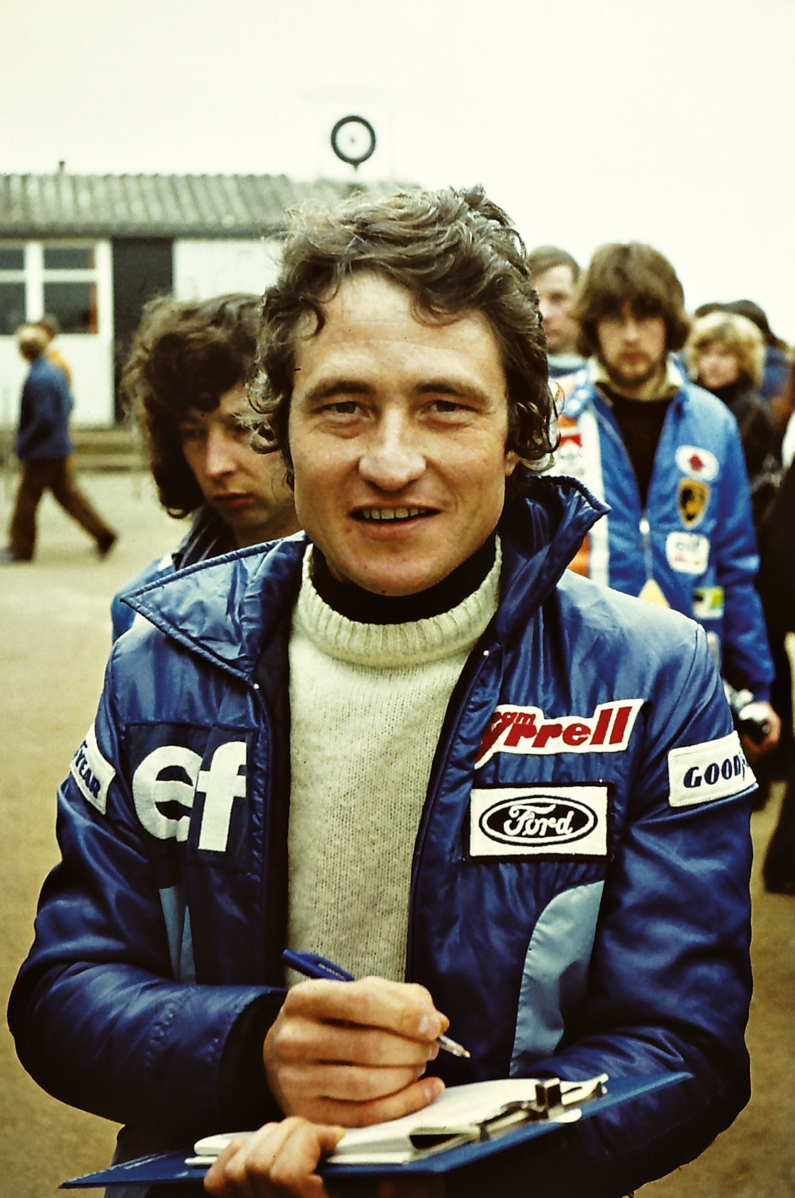 Tyrrell's Patrick Depailler takes some notes, presumably in-between signing autographs in the open paddock. He would finish fifth