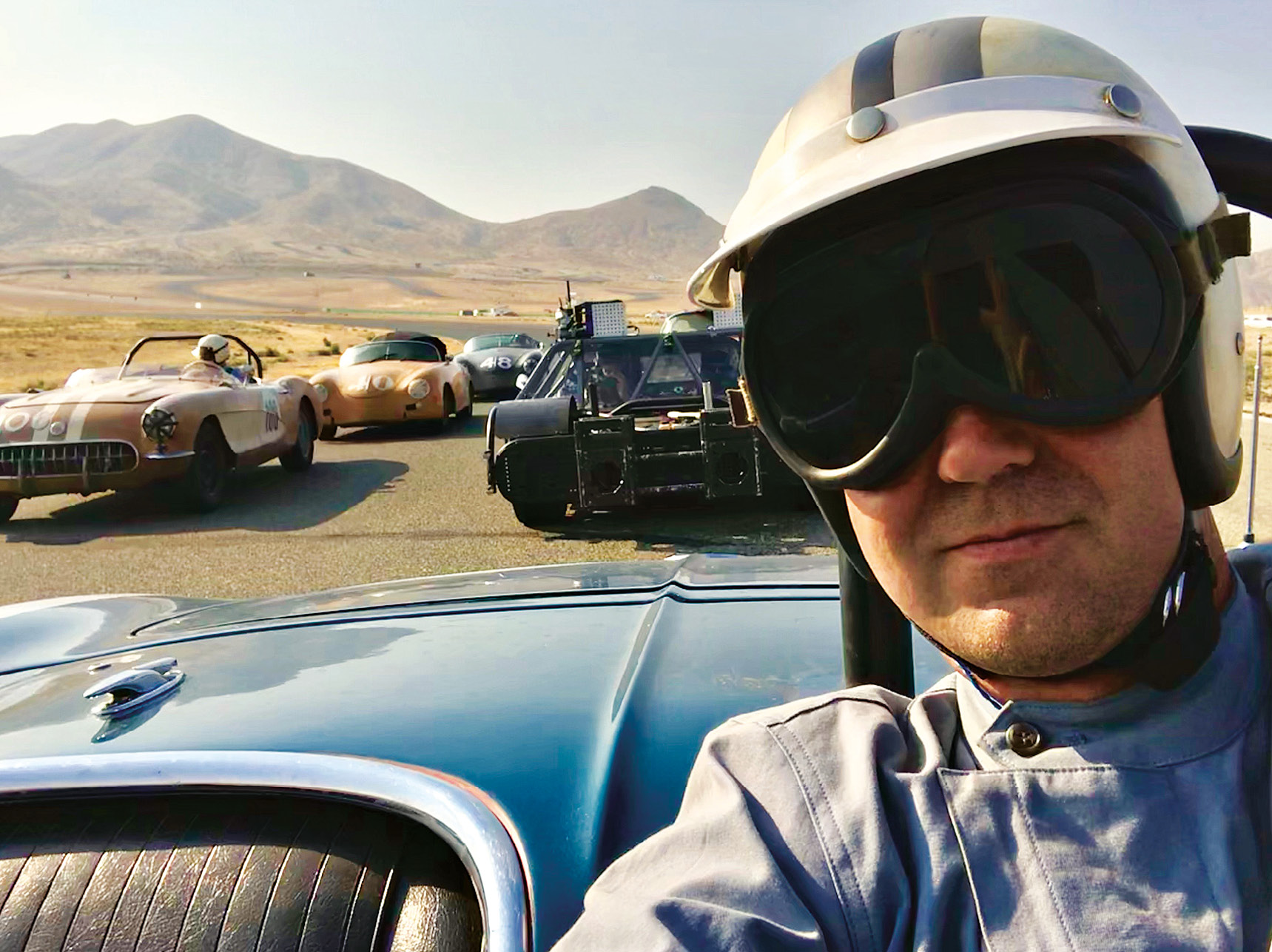 Hill on board a Corvette ready to recreate a race at Willow Springs Raceway, with filming vehicle behind.