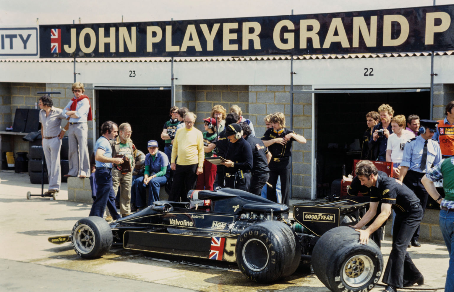 Silverstone 1977: Andretti changes tyres during practice; note Motor Sport's Jenks watching