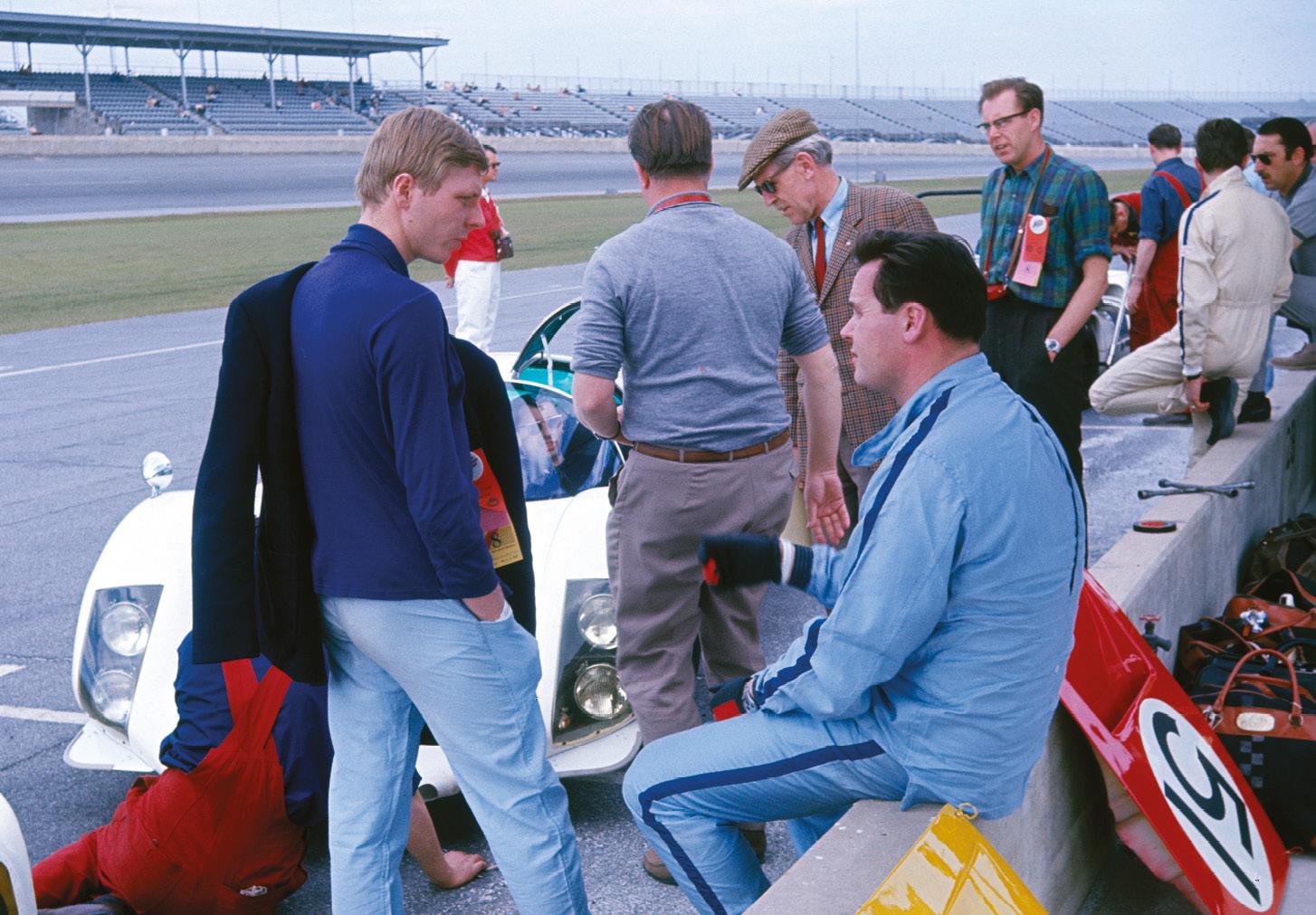 Gijs van Lennep (blue jacket) in '67 Daytona Porsche pit talks to Udo Shütz sat on the pit wall. Behind, Huschke von Hanstein (cap).